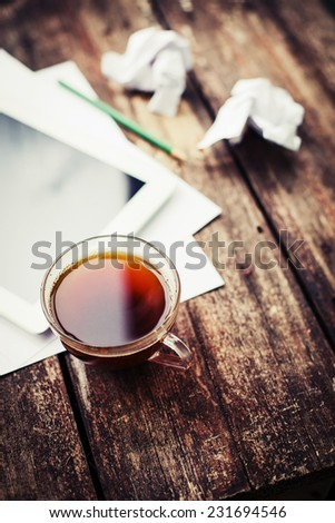 Digital tablet with note paper and cup of tea on old wooden desk. Simple workspace or coffee break in morning/ selective focus  - stock photo