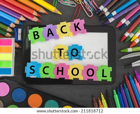 Digital Tablet With School Supplies On Black Background. - stock photo