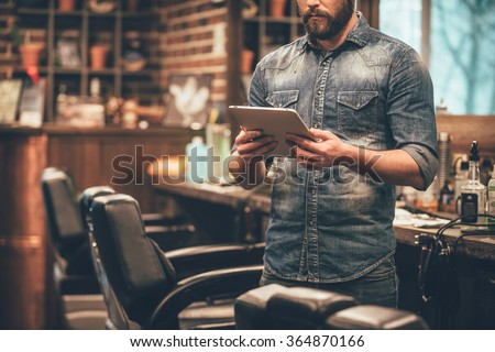 Digital technologies in any business. Close-up of young bearded man holding digital tablet while standing at barbershop - stock photo
