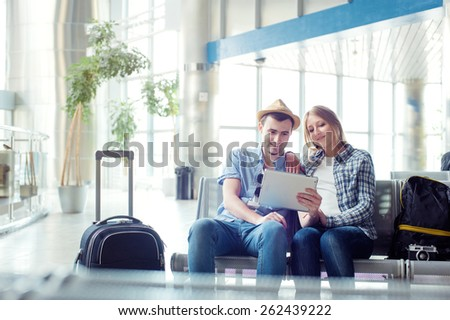 Digital technology and traveling. Young loving couple in casual wear using tablet computer while sitting in the airport terminal waiting for boarding. - stock photo