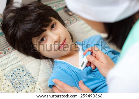 digital thermometer in the hands of a doctor. Temperature measurement in the child. home medicine. focus on thermometer - stock photo