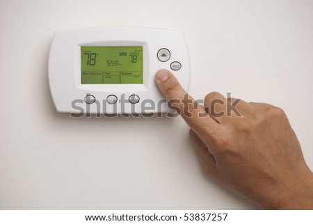 Digital Thermostat with a male hand, set to 78 degrees Fahrenheit. Saved with clipping path for thermostat and hand combined. - stock photo