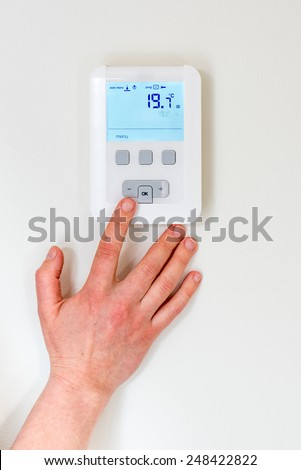 digital thermostat with finger pressing button - stock photo