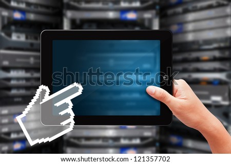 Digital touch pad in data center room and digital hand - stock photo
