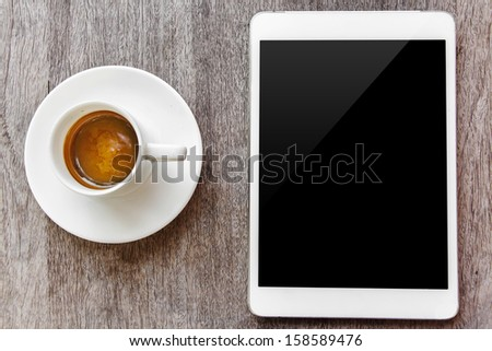 digital white tablet and coffee cup on wooden table  - stock photo