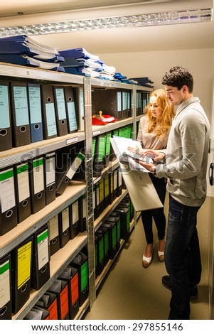 digitalization: handsome young man is entering data into a digital tablec pc while attractive woman checking documents in the company archives - concept for digitalization or modern storage - stock photo