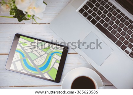 Digitally generated image of map against tablet on desk - stock photo
