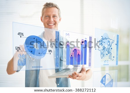 Digitally generated image of pie chart and bar graph against smiling businessman holding a laptop
