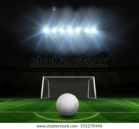 Digitally generated white leather football against football pitch and goal under spotlights - stock photo