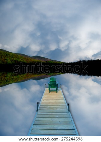 Digitally manipulated image of an adirondack chair sitting on the end of a dock in a cloud reflected lake. - stock photo