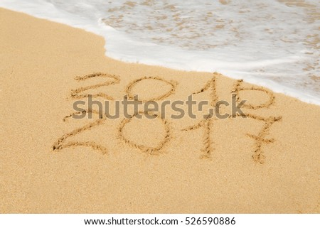 digits  2016 and 2017 on the beach sand - concept of new year,vacation,travel  and passing of time
