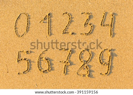 Digits from zero to nine, drawn on the sand beach. - stock photo