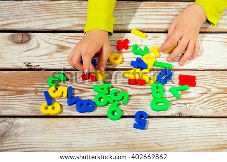 Digits on the table. Child takes numbers - stock photo