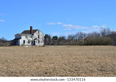 Dilapidated house in the middle of a field - stock photo