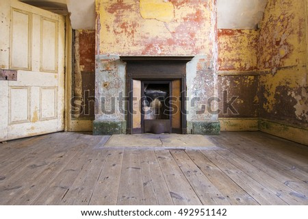 Dilapidated interior of historic English fort fireplace and worn wooden floor