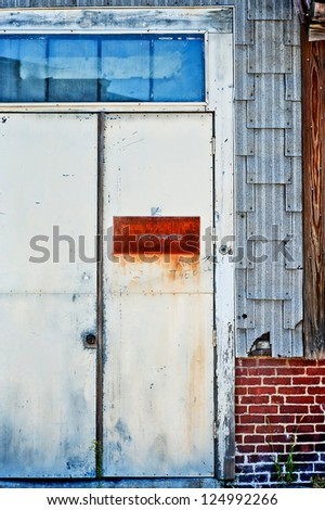 Dilapidated old metal door to an industrial building.