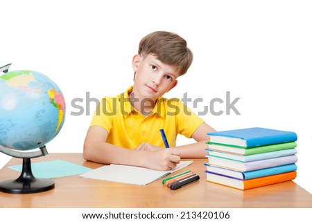 diligent pupil at the table with textbooks, notebook and globe - stock photo