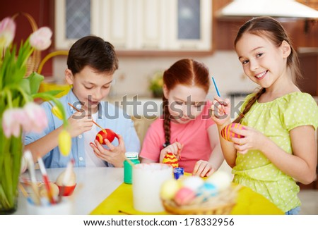 Diligent pupils painting Easter eggs - stock photo