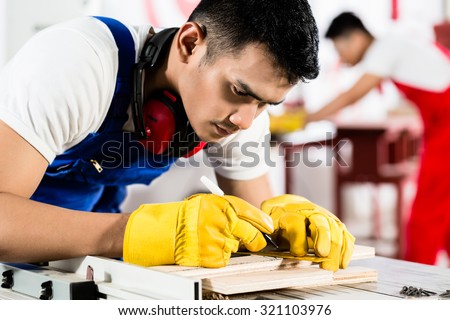Diligent worker in factory working on wood, in the background his colleague is cutting a piece - stock photo
