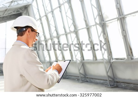 Diligent worker, Pleasant professional architect holding folder and making sketching while standing half turned - stock photo