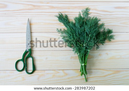 Dill and scissors on wooden background