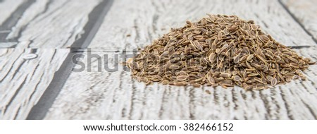 Dill herb seeds over wooden background