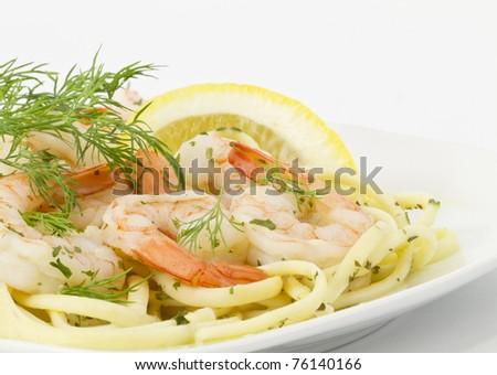 Dill Sprigs and lemon slice provide garnishes for shrimp scampi served over spaghetti pasta on white serving plate - stock photo