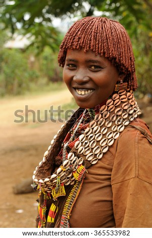 DIMEKA, OMO VALLEY, ETHIOPIA - JULY 27: Portrait of the woman from Hamer people resting by the fence in transit to the local marketplace in Dimeka, Omo valley in July 27, 2013