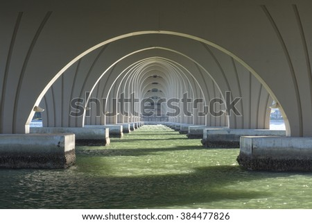 Diminishing perspective of support arches under highway 682 bridge connecting Isla del Sol and St. Pete Beach in Florida - stock photo