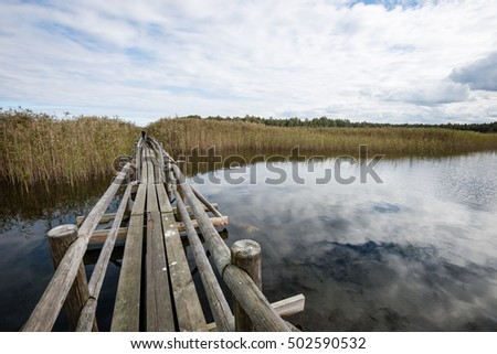 Diminishing perspective of wooden suspension footbridge over river in autumn