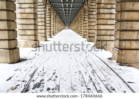 Diminishing perspective under bercy bridge in Paris with footprints on the fresh snow in the stone alleyway.  - stock photo