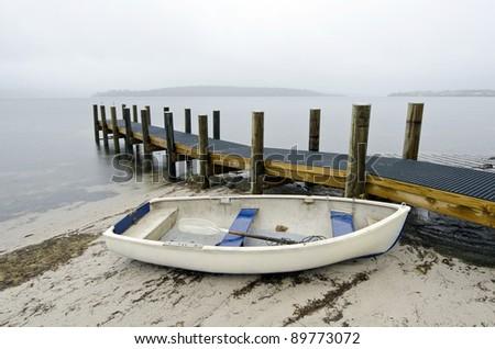 Dinghy and jetty in rain. East coast near St Helens, Tasmania, Australia - stock photo