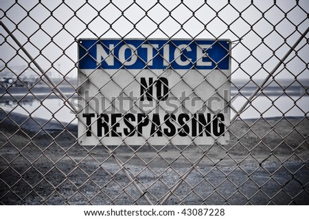 Dingy No Trespassing Sign in Front of Protected Area