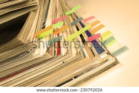 Dingy sepia-style photo of pile of old magazines with bookmarks - stock photo