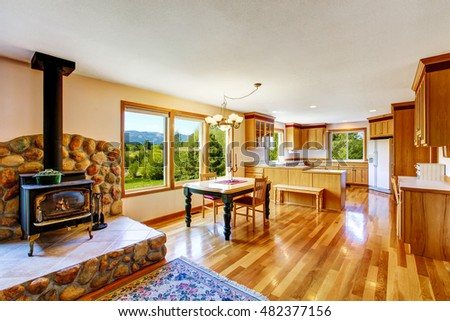 Dining and kitchen room interior and old style fireplace with stone decor. Open floor plan . Northwest, USA