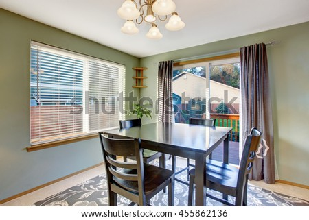 Dining area in green tones with black table set and carpet floor