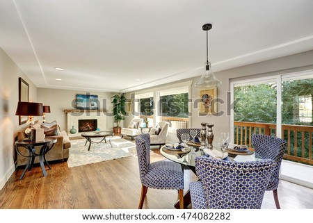 Dining area with blue chairs and elegant table setting. View of living room. Glass doors to the balcony. Northwest, USA