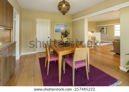 Dining area with wooden table adjacent living room within mid century home. - stock photo
