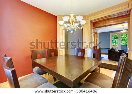 Dining room in red and blue and large wood table.