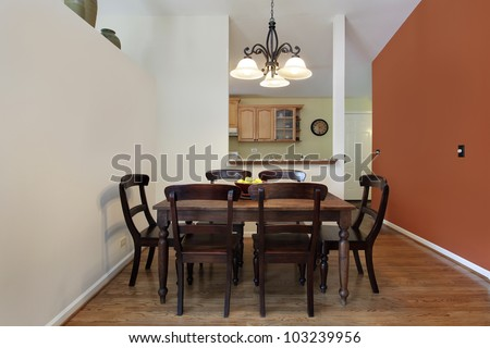 Dining room in suburban home with orange wall - stock photo