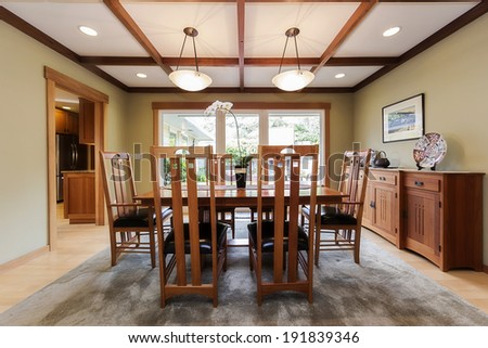 Dining room interior with cherry wood framed view window, ceiling, chair table and chestnut credenza. - stock photo