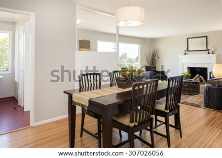Dining room table in dark wood with living room with fire place, chairs and copy space for art.  - stock photo