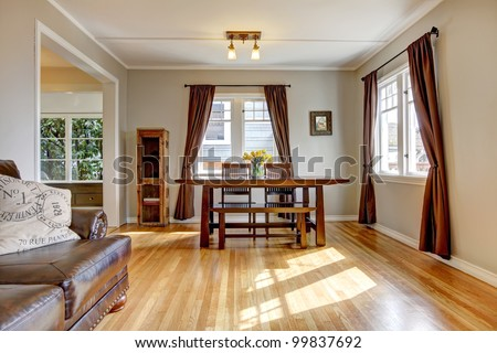 Dining room with brown curtain and hardwood floor and leather sofa. - stock photo