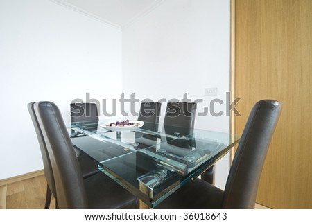 dining room with contemporary minimalistic table and glass table top - stock photo