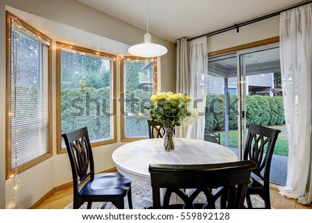 Dining Room With Curved Window Wall And Glass Sliding Doors Leading Out To Deck Yard