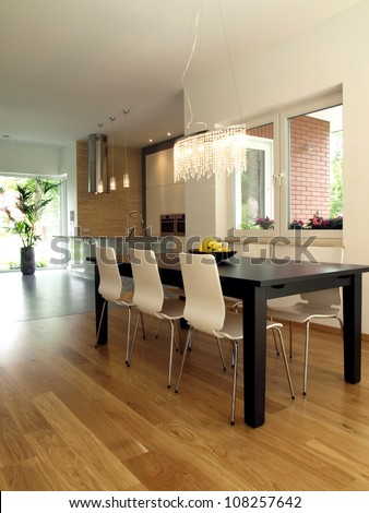 Dining room with dark table and bright chairs - stock photo