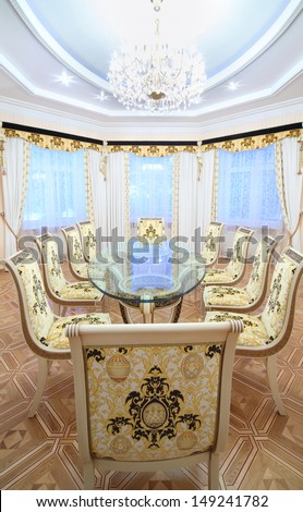 Dining room with luxury gilt furniture and beautiful table with glass top in classic style. - stock photo