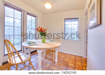 Dining room with orange tiles on the floor and large french door to the garden.