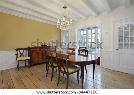 Dining room with white ceiling wood beams and gold walls - stock photo