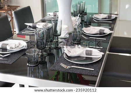 dining table and comfortable chairs in modern home with elegant table setting - stock photo
